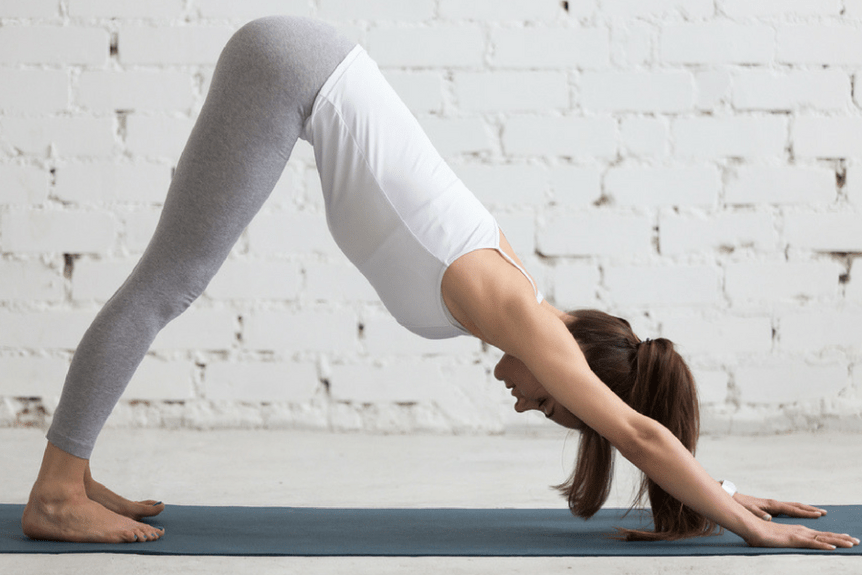 woman doing downward dog yoga pose eating disorder relief