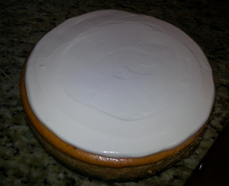 Spread the sour cream topping over the top of the cheesecake.