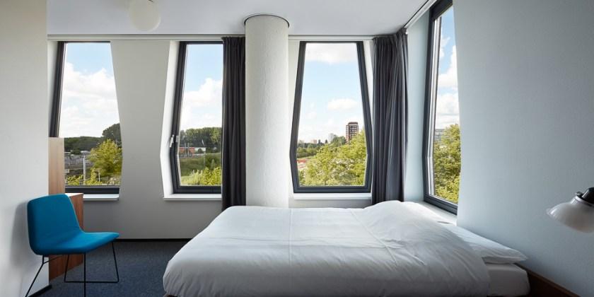 Hotelzimmer-Bett-Stuhl-Fensterseite