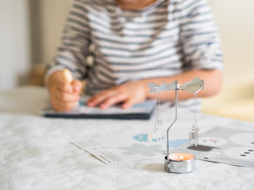 DIY Weihnachtskarten mit Fingerabdruck Mädchen beim Prickeln mit Teelicht
