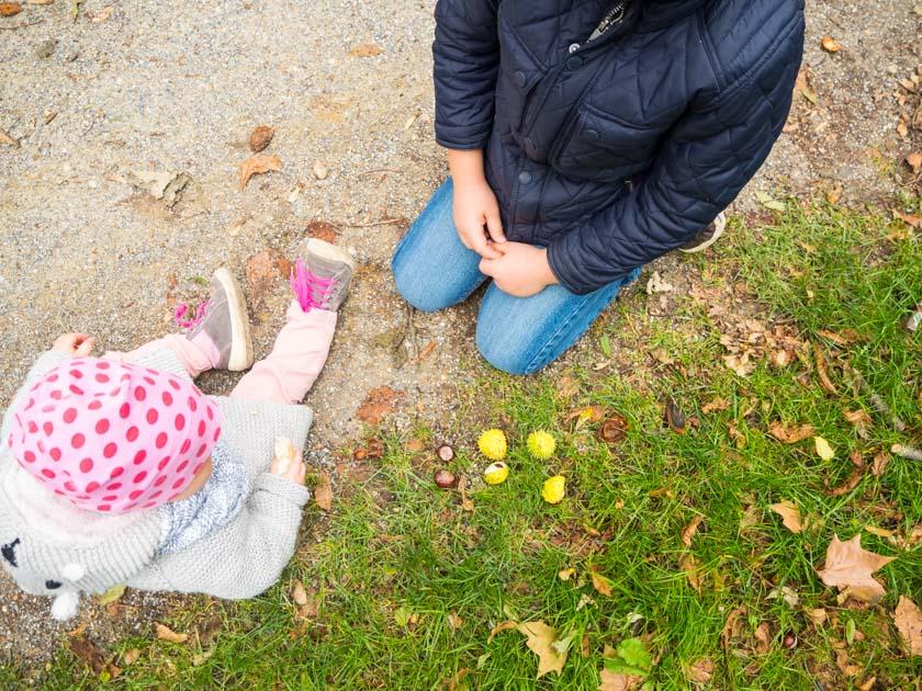 Herbstaktivitäten mit Kindern Kinder sitzen am Parkweg