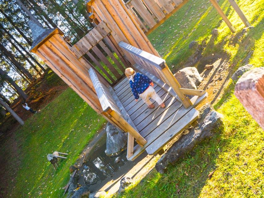 Familienurlaub am Bauernhof kleines Mädchen wandert Holzturm hinauf