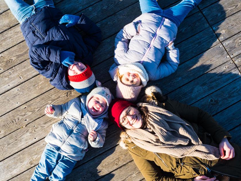 Mit Kindern gesund durch den Winter_Mama mit drei Kindern am Steg liegend