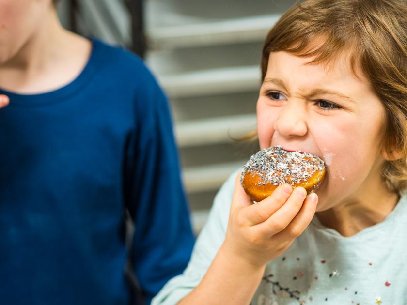 Krapfen backen mit Kindern_Mädchen Krapfen essend