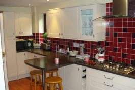 new kitchen with breakfast bar and red wall tiles
