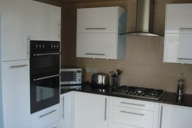 completed kitchen conversion with glossy white fixtures