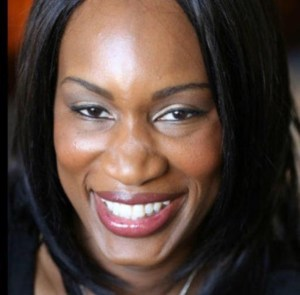 Image is a picture of a smiling Black woman (me!) gazing at the camera.