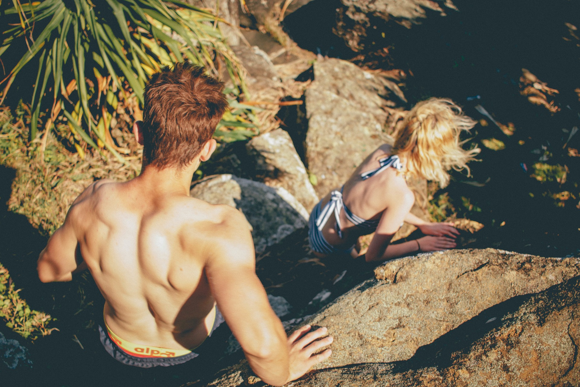 Young man climbs down rocks with attractive young woman