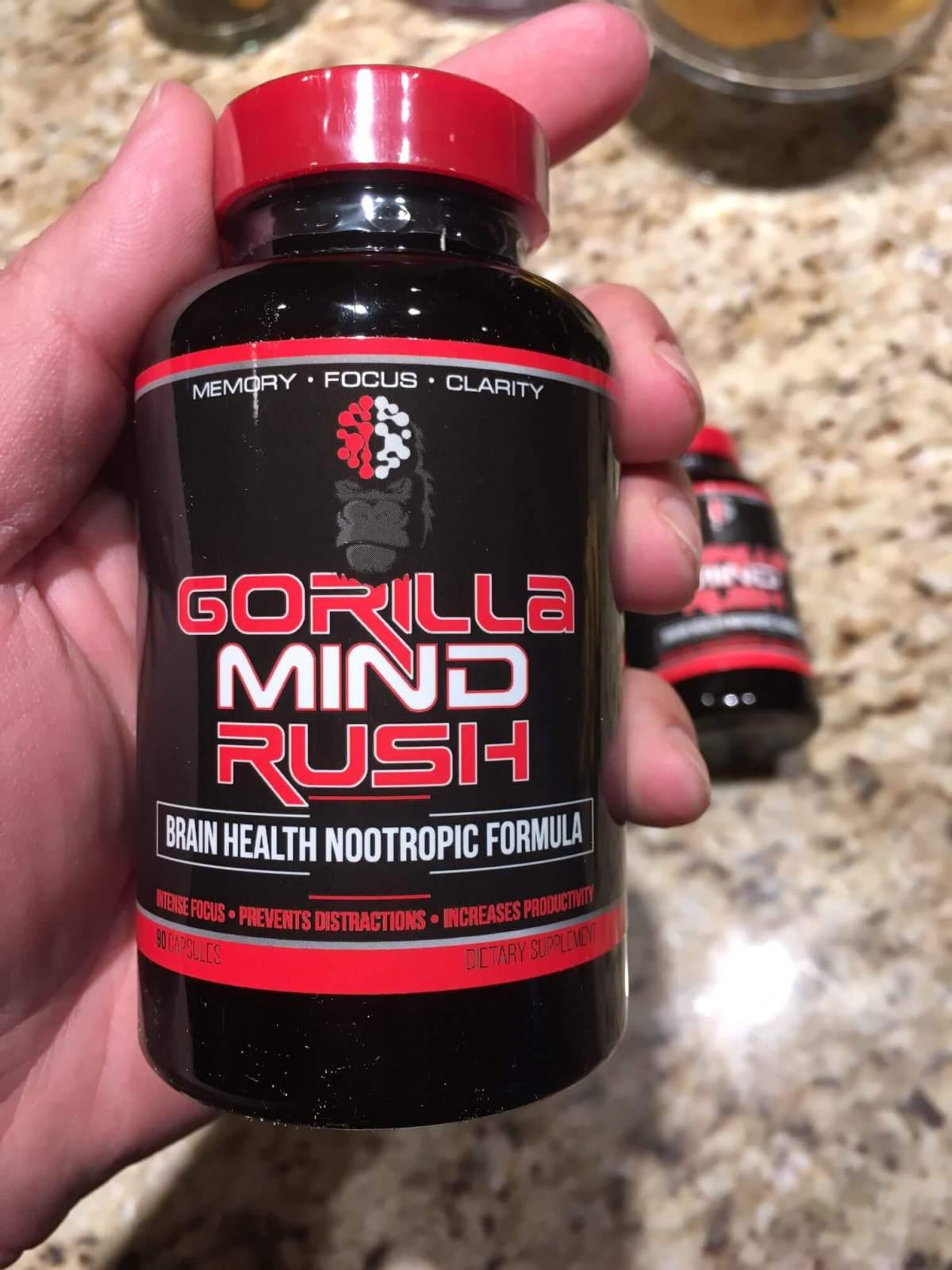 Left hand holding Gorilla Mind Rush Supplement
