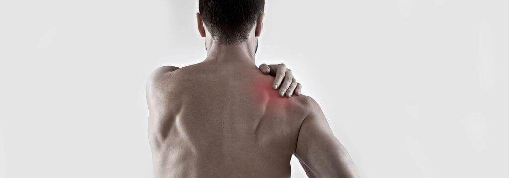 bodybuilder holding sore rear deltoid muscle