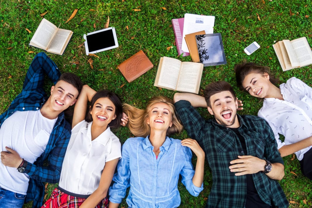 college students on grass laughing