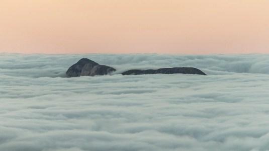 Un îlot de rocher dépasse de la mer de nuage peu avant le lever du soleil