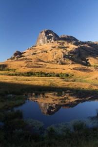 Une mare sert de miroir pour réfléter ce monolithe rocheux au lever du soleil