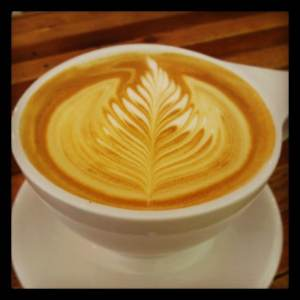 cup of latte with leaf artwork in the fom
