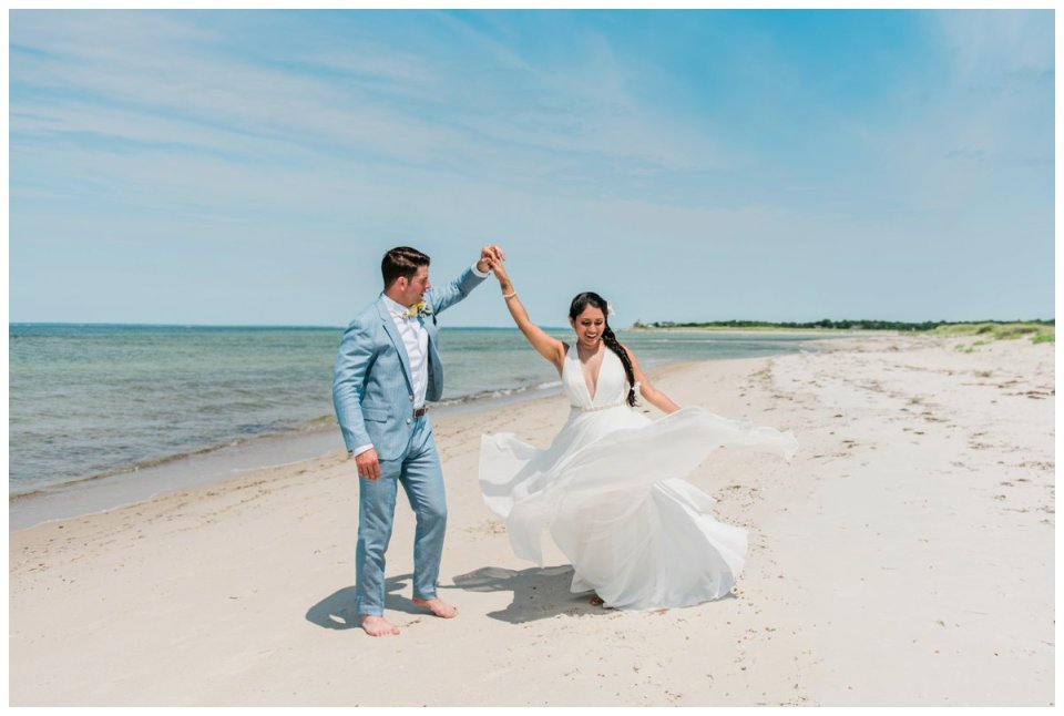A couple dancing on the beach in Falmouth after their intimate summer wedding ceremony overlooking Buzzards bay