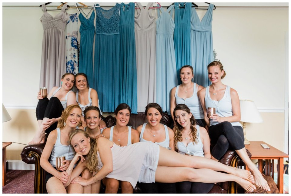 Warren Conference Center girls getting ready wearing matching yoga pants and blue tank tops with blue and grey mixed style bridesmaid dresses hanging