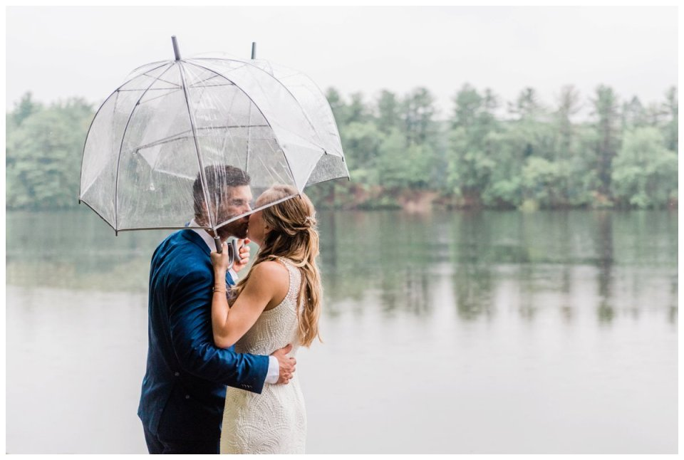 bride and groom kissing under matching umbrellas at Warren Conference Center along the waterfront