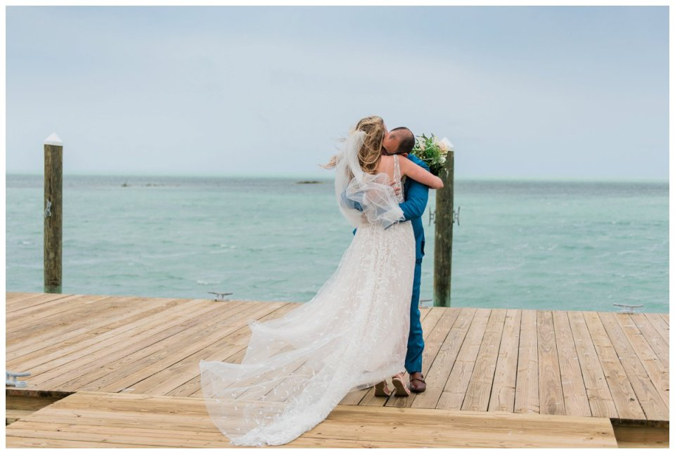 Bride and groom share a first look at the end of a pier at their amara cay resort destination florida