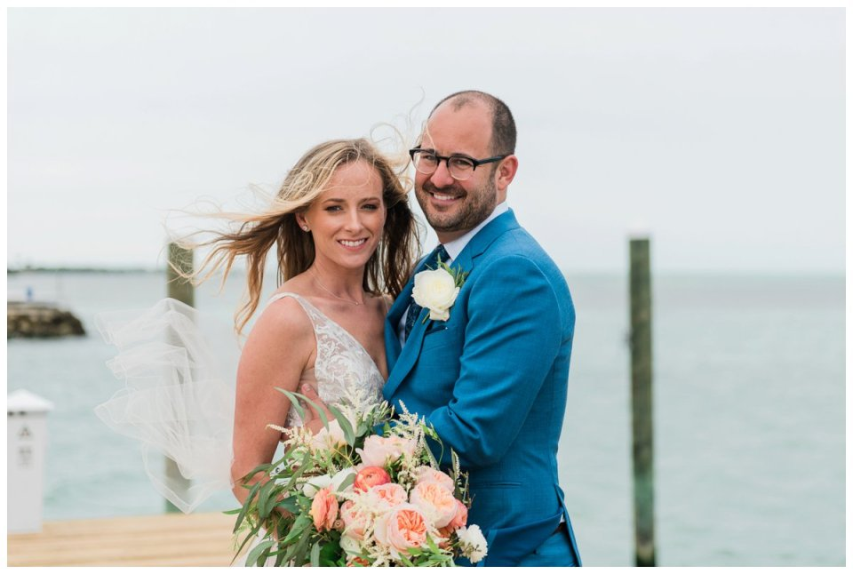 bride and groom portraits at the end of a pier at amara cay