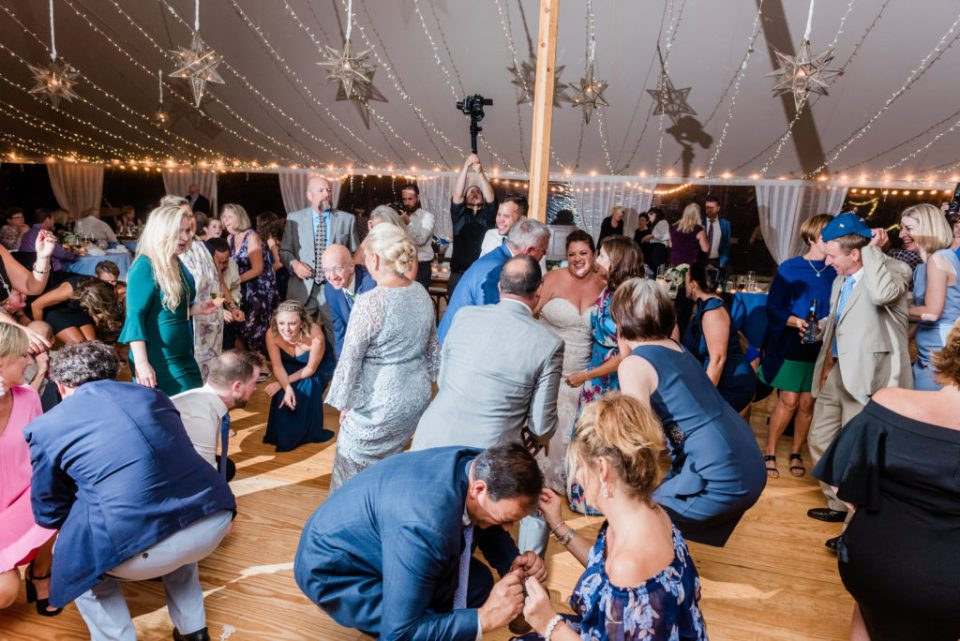 getting down dancing at the wedding reception under the tent