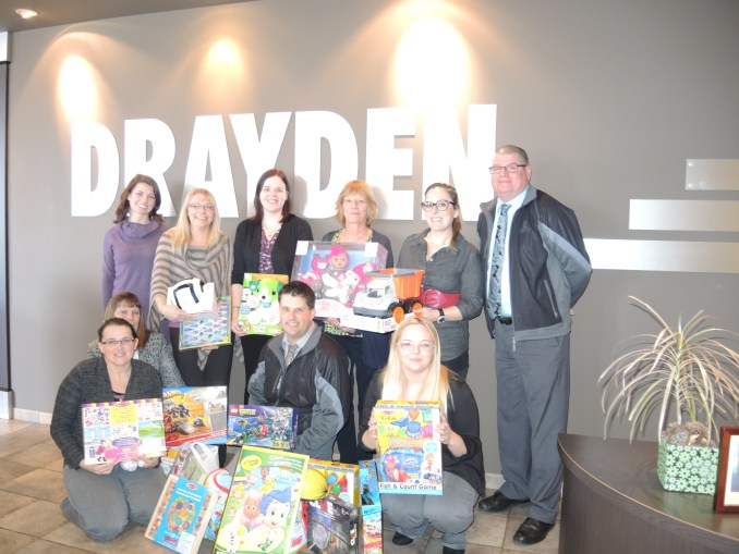 Midstream Support Society President Susan Swanson (far left), Morinville Drayden Insurance  Branch Manager Blair Shepherd ( far right) and staff pose with some of the toys Drayden employees donated to the Midstream Support Society Dec. 10 for their Santa Store. The employees decided to buy for the kids this year instead of a gift exchange.