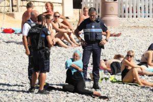 仏ニースのPromenade des Anglaisで、警察が彼女に青い長袖のトップを除去を促しているところ(2016.8.23)