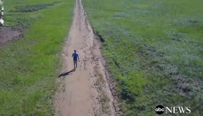 man walking on path aerial shot