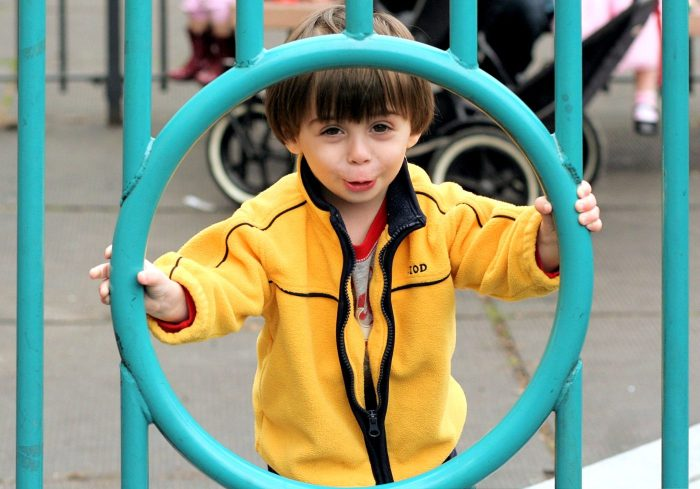 Child smiling while looking through a circular opening at a playgrounf