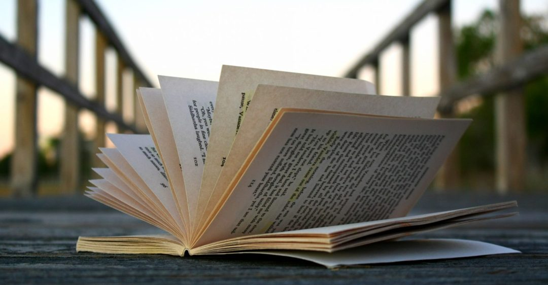 Open book sitting on a wooden bridge, pages flapping
