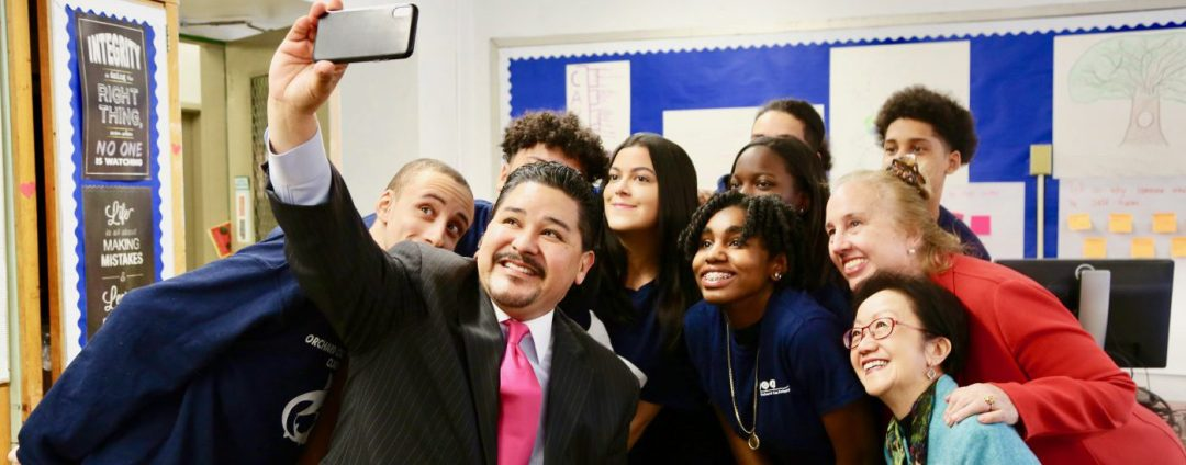 Chancellor Carranza holding up a smartphone for a selfie with students and public officials