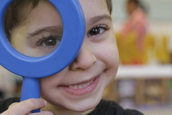 A kindergartener holding up a toy magnifying glass to his face.