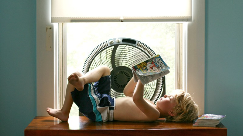 Child lying down on top of a TV stand next to a window fan while reading a book