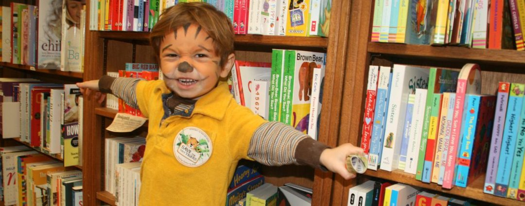 Child with lion facepaint standing next to a row of bookcases