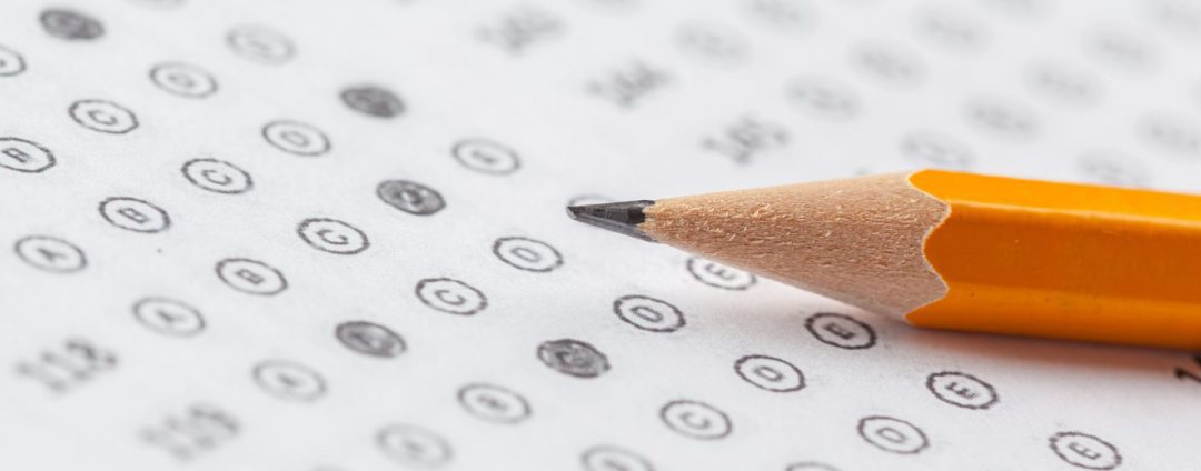Close up of a pencil laying on top of a standardized exam answer sheet.