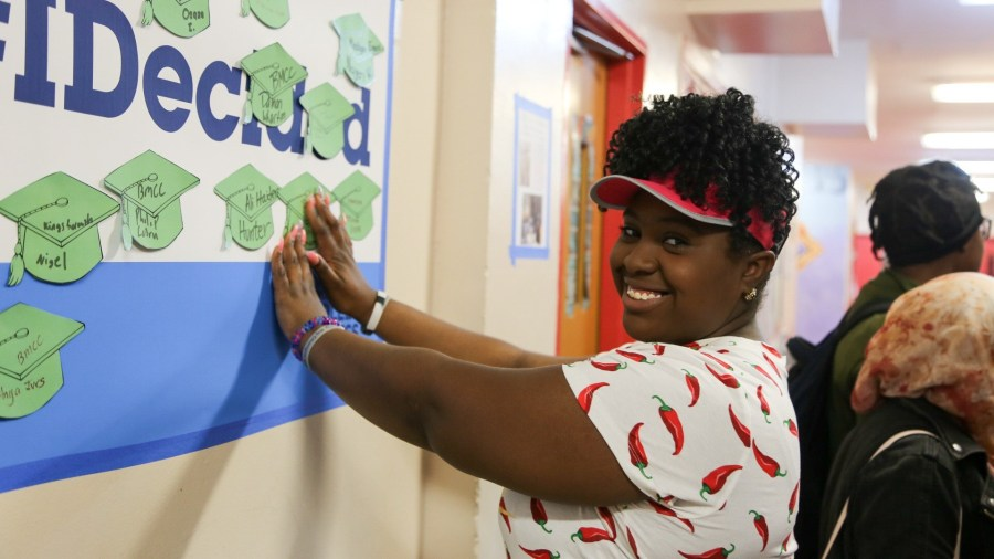 Student posting a paper cutout of a small graduation cap that features the name of the college she will be attending in the next school year.