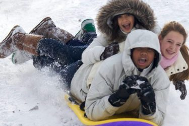 Three kids sharing one sled as it goes downhill in Central Park on a snowy day.