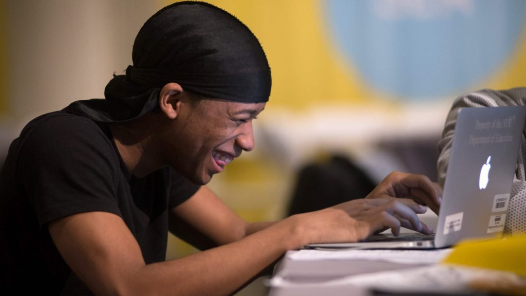 Student laughing while working on their school laptop