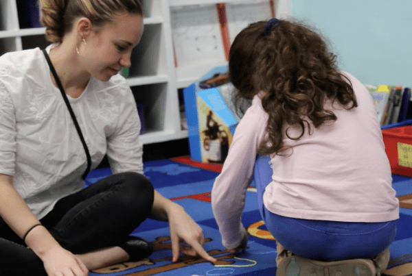 Adult sitting with child inside a classroom's carpeted play area.