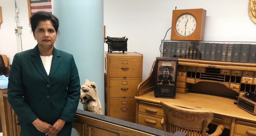 Sunita Mahabir Stands in front of old desk at DOEs Facilities Office in Queens