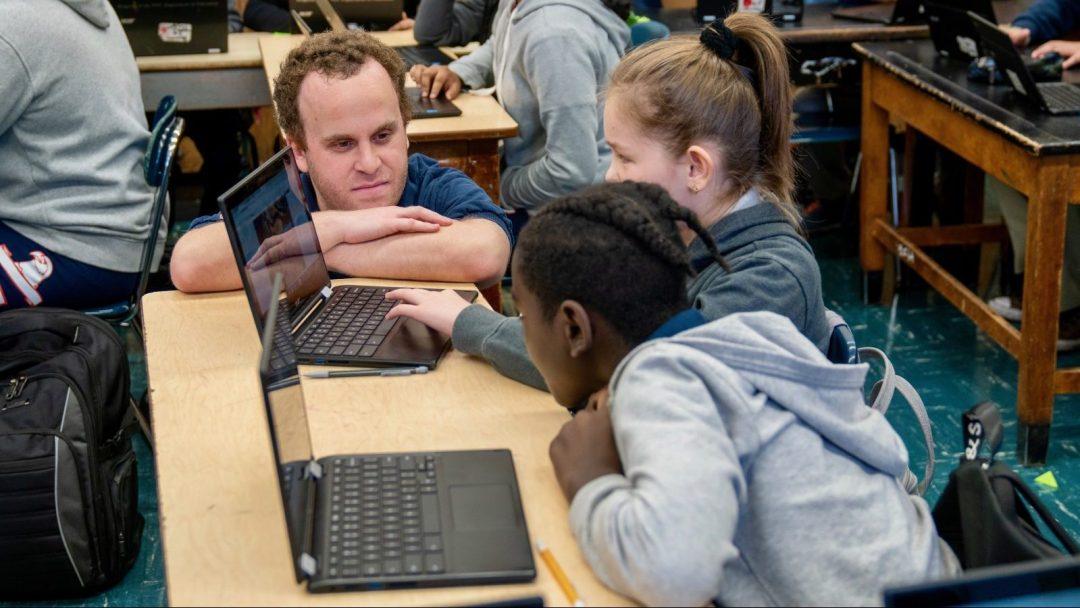 CS Teacher, Ross Berman, leaning down to help a pair of CS students
