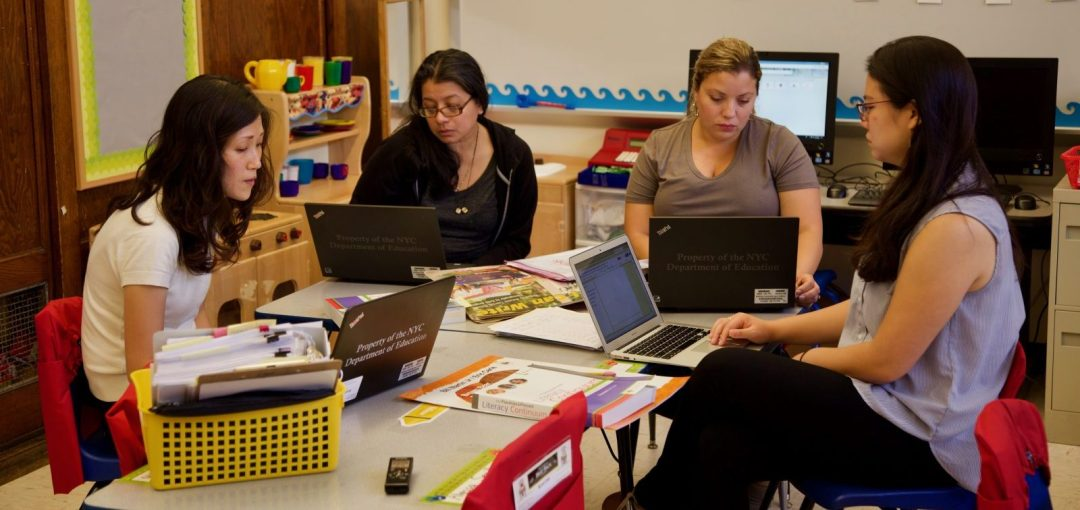 Annie Kim working at a table with three other teachers