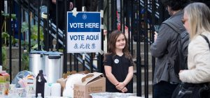 """Young girl with a """"Vote Here"""" pin standing outside of a polling place"""