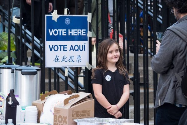 "Young girl with a ""Vote Here"" pin standing outside of a polling place"