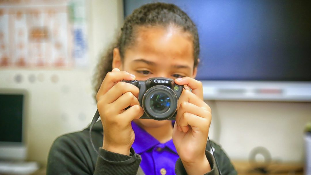 Student pointing a DSLR camera at the viewer