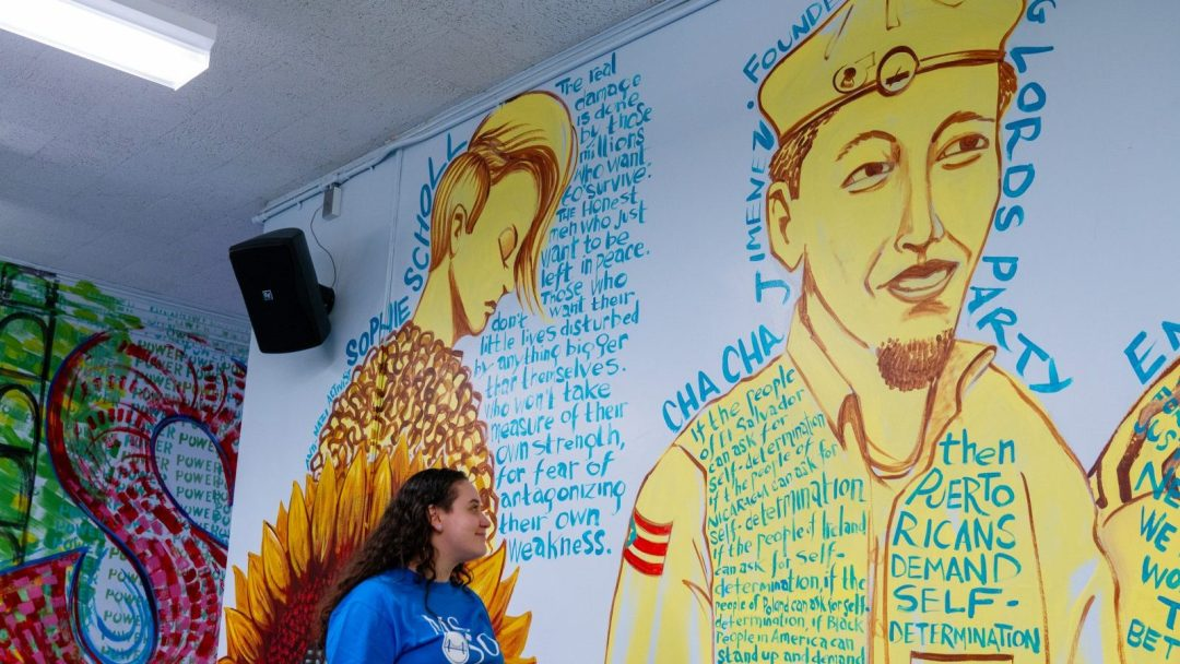 Miana Vega looking at mural of Young Lords at M.S. 50