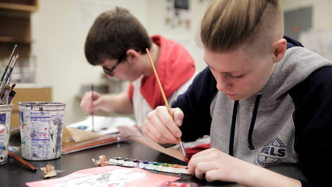 Two students painting with watercolors inside art classroom