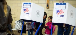 Parent at a voting booth in NYC with two young children