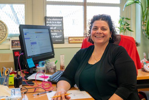Principal Francine Marsaggi sits at desk