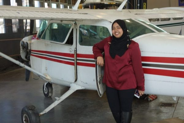 Sadia Ahmed standing by an airplane at Aviation High School