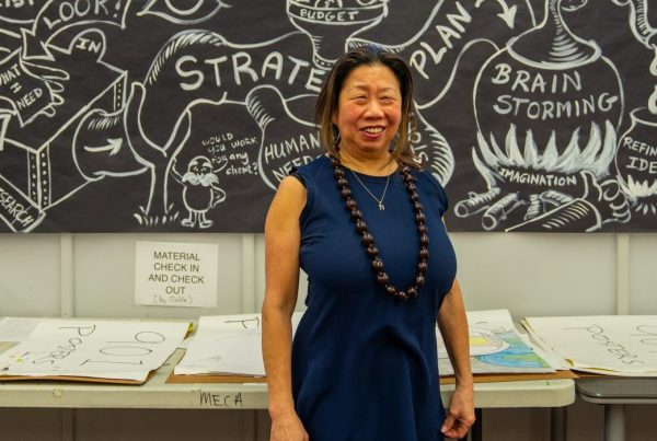 Carol Sun smiling while standing in front of a student mural dedicated to the creative process
